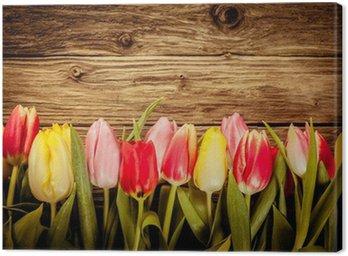 Beautiful fresh tulip border on rustic wood