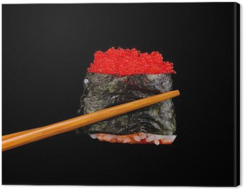 holding sushi with chopsticks isolated on black