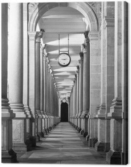 Long colonnafe corridor with columns and clock hanging from ceiling. Cloister perspective. . Black and white image.