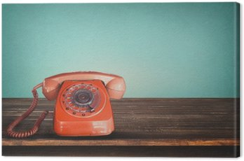 Canvas Print Old retro red telephone on table with vintage green pastel background