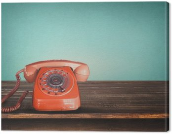 Old retro red telephone on table with vintage green pastel background Canvas Print
