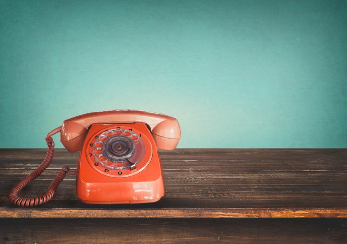 Canvas Print Old retro red telephone on table with vintage green pastel background -