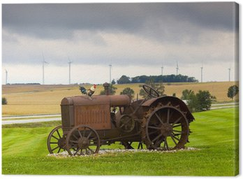 Canvas Print Old rusty tractor with wind turbines in the background.