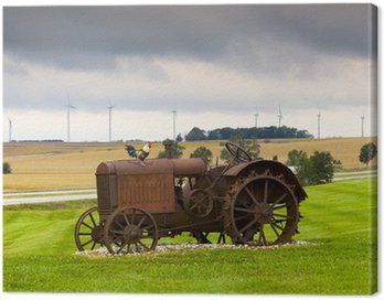 Old rusty tractor with wind turbines in the background.