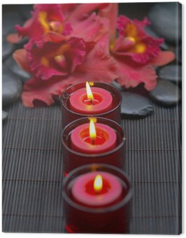red orchid with row of candle and zen stones on mat