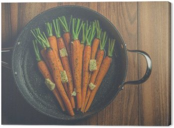 Rustic carrots in a large pan on wood