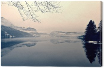 Canvas Print Snowy winter landscape on the lake in black and white. Monochrome image filtered in retro, vintage style with soft focus, red filter and some noise; nostalgic concept of winter. Lake Bohinj, Slovenia.
