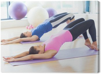 Two sporty women stretching body at yoga class