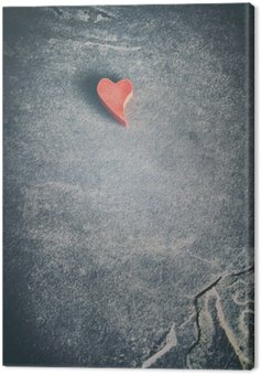 Vintage toned wooden red heart on grunge stone background, shallow depth of field, space for text. Canvas Print