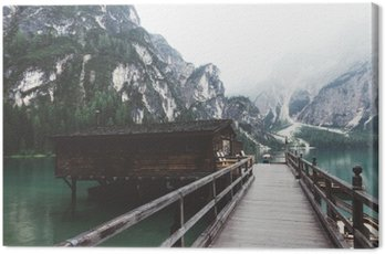 wooden jetty on Braies lake with mountains and trees