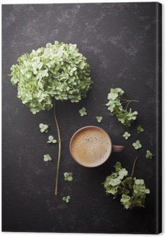 Canvas Samenstelling met een kopje koffie en gedroogde bloemen hortensia op zwart vintage tafel van boven, plat