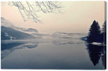 Canvas Snowy winter landschap op het meer in zwart-wit. Zwart-wit beeld gefilterd in retro, vintage stijl met soft focus, rode filter en wat lawaai; nostalgische concept van de winter. Lake Bohinj, Slovenië.