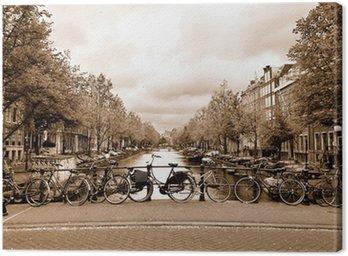 Canvas Uitzicht op het centrum van Amsterdam met fietsen op een brug