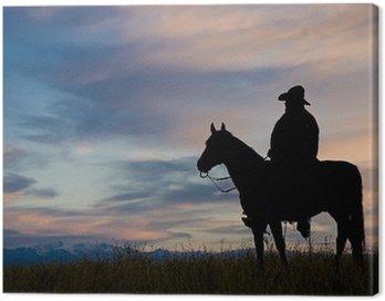Canvastavla Cowboy på hästryggen, silhouetted mot en gryning himmel
