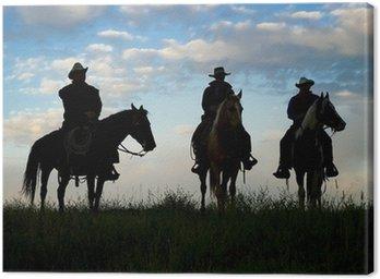 Canvastavla Cowboys till häst vid första ljus. Silhouettes