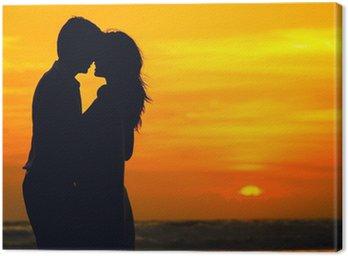 Canvastavla Förälskat par på havet stranden i solnedgången
