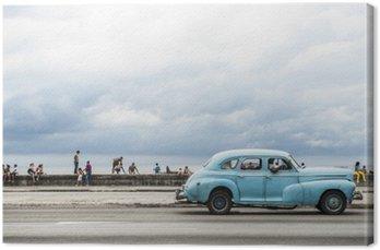 Canvastavla Havanna, Kuba - 18 maj 2011: Klassisk tappning amerikansk bil som tjänar som taxi kör längs havet Malecon, en populär plats för att umgås i centrala Havanna.