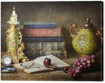 Canvastavla Klassisk stilleben med antikviteter, vintage böcker, gamla rör, glasögon, fickur och druvor på rustika träbord.