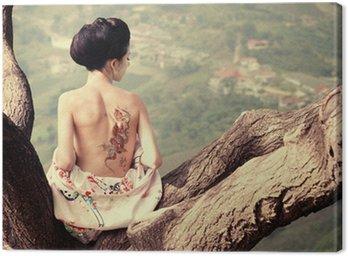 Canvastavla Kvinna med orm tatuering sitter på trädgren