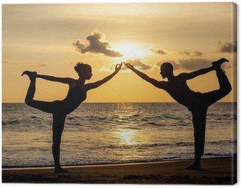 Canvastavla Par tränar yoga tillsammans stretching medan solnedgången