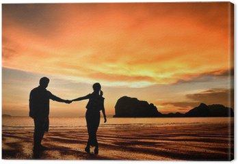 Canvastavla Romantiska par håller varandra i handen vid solnedgången på stranden