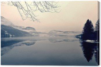 Canvastavla Snöiga vinterlandskapet på sjön i svart och vitt. Svartvit bild filtreras i retro, vintage-stil med mjukt fokus, rött filter och vissa buller; nostalgiska begreppet vinter. Lake Bohinj, Slovenien.