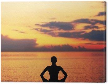 Canvastavla Sunset meditation. Silhuetten av en kvinna som gör yoga övning.