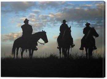 Canvastavla Tre cowboys till häst silhuett mot gryningen sky