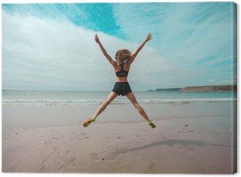 Canvastavla Ung kvinna gör stjärna hoppar på stranden