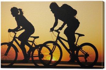 Canvastavla Unga par ridning cyklar vid solnedgången.