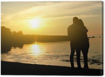 Canvastavla Ungt par njuter av solnedgången. Två silhuetter.