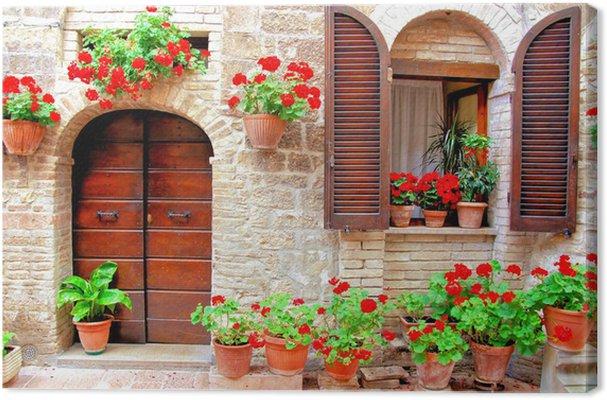 cuadro en lienzo frente de la casa italiana con macetas de flores