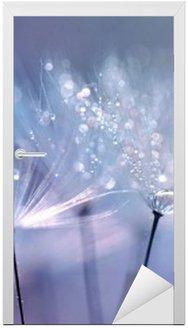 Deursticker Mooie dauw druppels op een paardebloem zaad macro. Mooie blauwe achtergrond. Grote gouden dauw druppels op een parachute paardenbloem. Zachte dromerige tender image artistieke vorm.