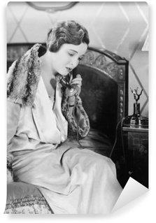 Vinyl Fotobehang Jonge vrouw zittend op haar bed in de slaapkamer, op de telefoon spreekt