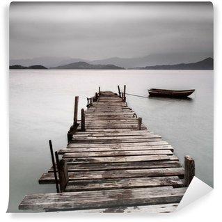 Vinyl Fotobehang Kijkt uit over een pier en een boot, lage verzadiging