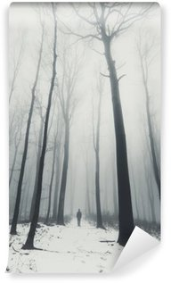 Vinyl Fotobehang Man in het bos met hoge bomen in de winter