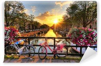 Vinyl Fotobehang Mooie zonsopgang over Amsterdam, Nederland, met bloemen en fietsen op de brug in het voorjaar