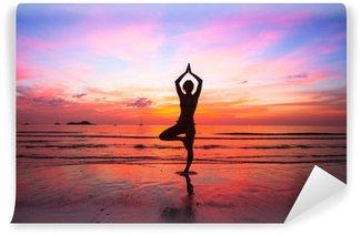 Vinyl Fotobehang Silhouet vrouw het beoefenen van yoga op het strand bij zonsondergang.