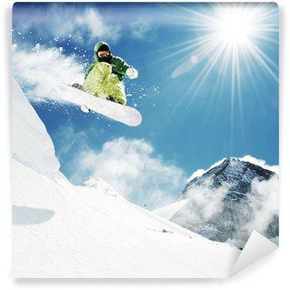 Vinyl Fotobehang Snowboarder bij sprong inhigh bergen