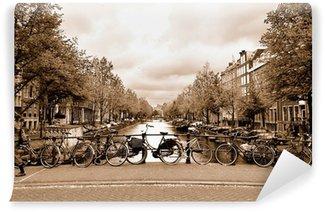 Vinyl Fotobehang Uitzicht op het centrum van Amsterdam met fietsen op een brug
