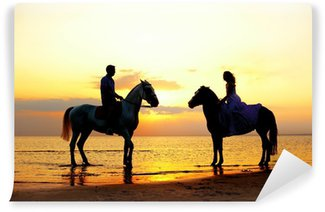Fotomural Estándar Dos jinetes a caballo al atardecer en la playa. Los amantes montan hors