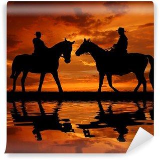 Fotomural Estándar Silueta de los vaqueros con caballos en la puesta del sol