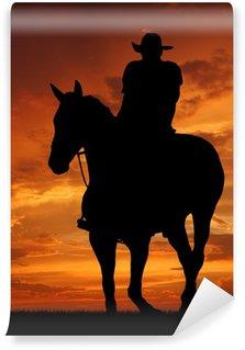 Fotomural Estándar Vaquero silueta en la salida del sol