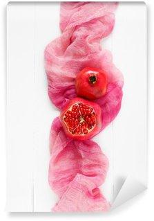 Vinyl-Fototapete Draufsicht auf eine reife Granatapfel auf einem rosa Stoff. Lebensmittel Mode minimal Stil. Nur Granatapfel