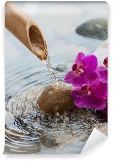 Vinyl-Fototapete Fließendem Wasser auf Steine neben Blumen