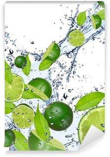 Vinyl-Fototapete Limes in Wasser fallen spritzen, isoliert auf weißem Hintergrund