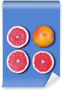 Vinyl-Fototapete Minimal-Design. Frische Grapefruit auf einem blauen Hintergrund
