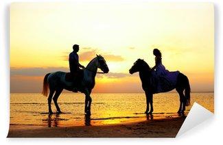 Vinyl-Fototapete Zwei Fahrer auf dem Pferd bei Sonnenuntergang am Strand. Liebhaber fahren hors