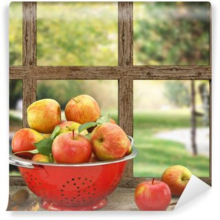Fototapet av Vinyl Äpplen i durkslag på trä fönster med utsikt