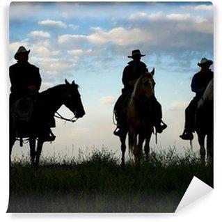 Fototapet av Vinyl Cowboys till häst vid första ljus. Silhouettes